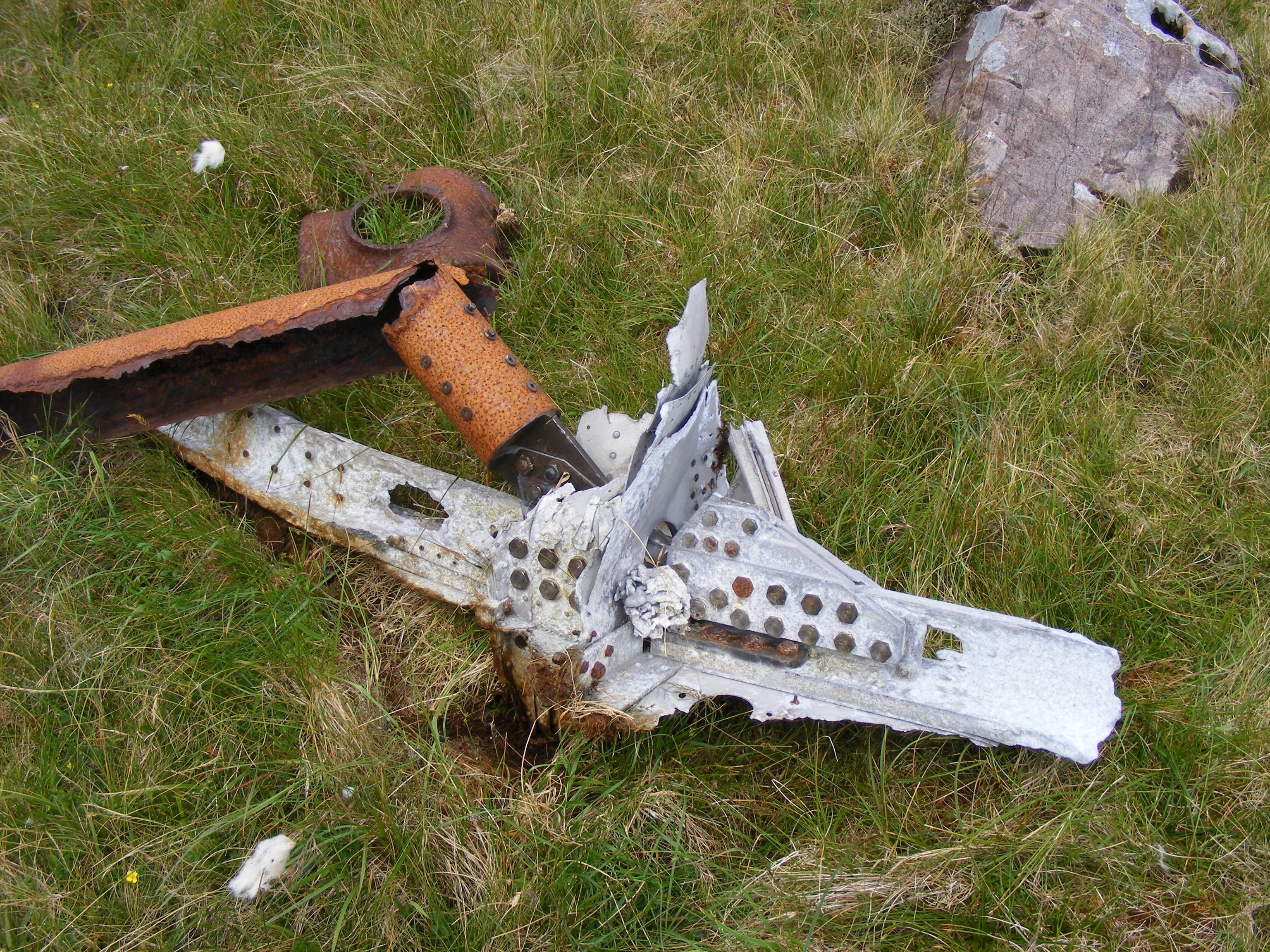 A piece of aircraft structure in the grass next               to the rocks.